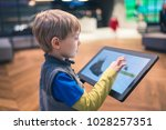 the boy buys shoes in the... | Shutterstock . vector #1028257351