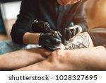 tattoo artist in black gloves...   Shutterstock . vector #1028327695