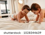 two baby girls lying on bed... | Shutterstock . vector #1028344639