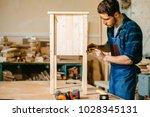 man measuring a wooden board... | Shutterstock . vector #1028345131