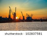 Cranes working at the port of Gdansk over sunrise. - stock photo