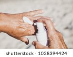 elderly woman smears her hands... | Shutterstock . vector #1028394424