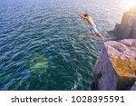 a man jumping off a cliff into... | Shutterstock . vector #1028395591