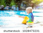baby with toy boat in swimming... | Shutterstock . vector #1028473231