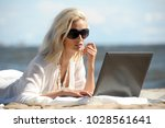 woman with netbook working near ... | Shutterstock . vector #1028561641