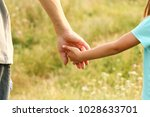 the parent holds the hand of a... | Shutterstock . vector #1028633701