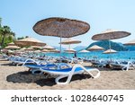 sun loungers on a beach in... | Shutterstock . vector #1028640745