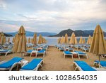 sun loungers on a beach in... | Shutterstock . vector #1028654035