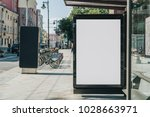 Small photo of Vertical blank white billboard at bus stop on city street. In the background buildings and road. Mock up. Poster on street next to roadway. Sunny summer day.