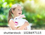 child playing with white rabbit.... | Shutterstock . vector #1028697115