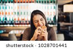 young woman eating fatty... | Shutterstock . vector #1028701441