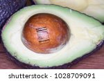 Small photo of Ripe avocado sliced in half with seed and nutrition fact label.