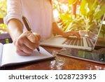 hand held pen on notebook and... | Shutterstock . vector #1028723935