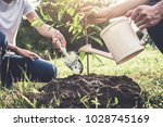 young couple planting the tree... | Shutterstock . vector #1028745169