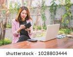 asian young girl open the purse ... | Shutterstock . vector #1028803444