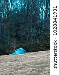 tent on a field in a forest in... | Shutterstock . vector #1028841931