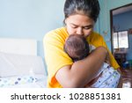 mother kissing her newborn baby ... | Shutterstock . vector #1028851381