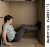 Small photo of Need more space concept. Full length of young man is sitting in cardboard box while pushing the wall with his feet and trying to move them. He is expressing irritation