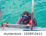 happy diver returns to the ship ... | Shutterstock . vector #1028912611