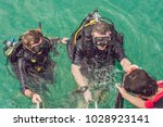 happy diver returns to the ship ... | Shutterstock . vector #1028923141