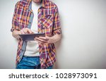 a man in jeans and a shirt is... | Shutterstock . vector #1028973091