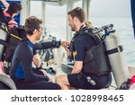 diving instructor helps a... | Shutterstock . vector #1028998465