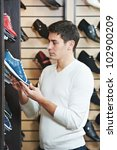 Young man choosing shoes during footwear shopping at shoe shop - stock photo