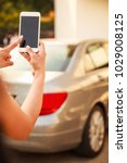 Small photo of Female Lady using app on smart phone device, technology concept. Lady hand using remote control to send signal to unlock car doors and trunk in the parking lots.