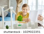 Small photo of Thirst for knowledge. Charming pre-ten boy studying a book dedicated to ecology while looking at the miniatures of trees, solar panels and wind turbines