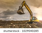 Small photo of Big yellow digger on gravel heap with big shovel