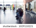 Small photo of Blurred background of travelers or tourists walking ,sitting on the seat and relaxing in hall area for wait time to travel other country or other city. Traveling style and holidays concept.