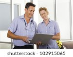 Young doctor talking with attractive nurse - stock photo