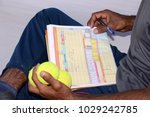 Small photo of A cricket score card with tennisballs