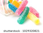 Small photo of closeup of traditional acidulated candies faling from glass container on white background