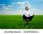 businesswoman practicing yoga at the meadow at sunny day - stock photo