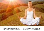 woman meditating in lotus pose | Shutterstock . vector #1029440065