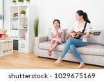 mom playing guitar on the sofa... | Shutterstock . vector #1029675169
