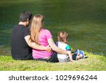 family sitting by the lake | Shutterstock . vector #1029696244