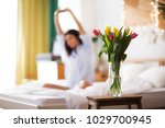 Small photo of Girl with flowers tulips sits on a bed. She has just woken up and have presented her a bouquet of flowers