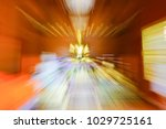 Small photo of Metaphysical effect Buddhist abstract zoom blur inside wooden Buddhist Temple with large golden Buddha with polished wooden floors and dark timber paneling.
