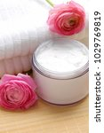 Small photo of Pink ranunculus with towel, cream on mat