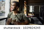 arabian sits by table near cup... | Shutterstock . vector #1029824245