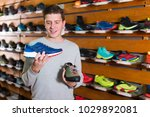 cheerful man chooses shoes in a ... | Shutterstock . vector #1029892081