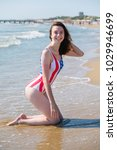 Small photo of Young girl in a swimsuit with the us flag is kneeling on the seaside fand looking at camera