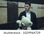 Small photo of Sad young guy holds a stuffed toy and waits for a lover.