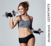 smiling athletic woman pumping... | Shutterstock . vector #1029979975