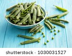 Green Peas In Pods On A Wooden...