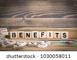 benefits. wooden letters on the ... | Shutterstock . vector #1030058011