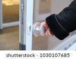 the hand opens the door by the... | Shutterstock . vector #1030107685