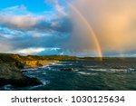 A vibrant rainbow arches across ...
